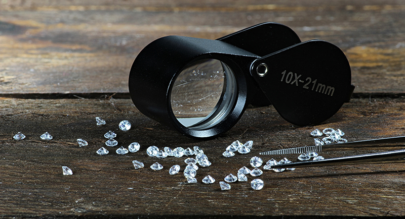 50537570 - cut diamonds with folding magnifier and tweezers on wooden background